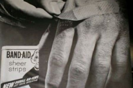 man ripping a band-aid off his hand